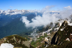 Nuvens acima dos picos de montanha de Cáucaso cobertos com a neve e a floresta Fotografia de Stock