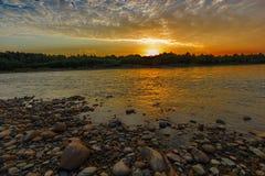 Nuvens alaranjadas da manhã sobre o rio Imagem de Stock