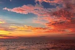 Nuvens alaranjadas do por do sol acima da água do mar fotos de stock