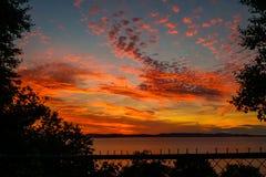 Nuvens alaranjadas no por do sol sobre a terra de acampamento Imagem de Stock