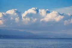 Nuvens brancas bonitas no céu azul, e mountins fotografia de stock
