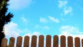 Nuvens brancas de fluxo em um céu azul e em uma cerca de piquete video estoque