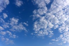 Nuvens brancas de surpresa da forma incomum no fundo do céu azul fotografia de stock
