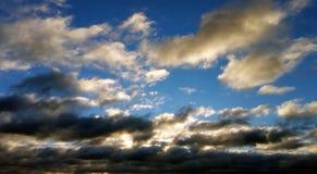Nuvens brancas e pretas contra o céu azul no por do sol Foto de Stock