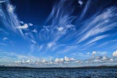 Nuvens brancas vagas fantásticas contra um escuro - flutuador do céu azul fotos de stock royalty free