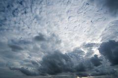 Nuvens com fundo, luz solar através do fundo muito escuro das nuvens da nuvem de tempestade escura Foto de Stock