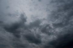 Nuvens com fundo, luz solar através do fundo muito escuro das nuvens da nuvem de tempestade escura Fotos de Stock