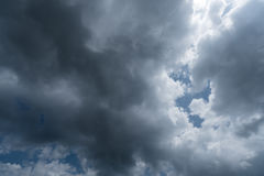 Nuvens com fundo, luz solar através do fundo muito escuro das nuvens de nuvens de tempestade escuras Imagens de Stock Royalty Free