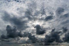 Nuvens com fundo, luz solar através do fundo muito escuro das nuvens de nuvens de tempestade escuras Imagens de Stock