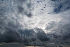 Nuvens com fundo, luz solar através do fundo muito escuro das nuvens de nuvens de tempestade escuras Foto de Stock Royalty Free