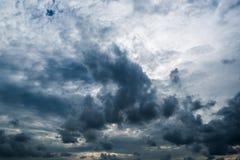 Nuvens com fundo, luz solar através do fundo muito escuro de nuvens de tempestade escuras, fundo preto das nuvens do céu de nuven Foto de Stock