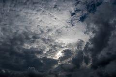 Nuvens com fundo, luz solar através do fundo muito escuro de nuvens de tempestade escuras, fundo preto das nuvens do céu de nuven Foto de Stock Royalty Free