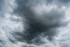Nuvens com fundo, luz solar através do fundo muito escuro das nuvens da nuvem de tempestade escura Imagem de Stock
