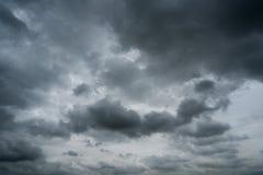 Nuvens com fundo, luz solar através do fundo muito escuro das nuvens da nuvem de tempestade escura Fotos de Stock Royalty Free