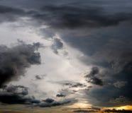 Nuvens com fundo, luz solar através do fundo muito escuro das nuvens da nuvem de tempestade escura Imagem de Stock Royalty Free