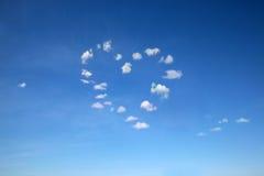 Nuvens dadas forma coração no céu azul Foto de Stock