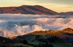Nuvens de aumentação no campo montanhoso no nascer do sol imagens de stock
