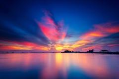 Nuvens de cúmulo alaranjadas e cor-de-rosa dramáticas no por do sol com o céu azul sobre a ilha com superfície da água calma e li imagem de stock royalty free