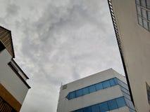 Nuvens de chuva entre construções foto de stock royalty free