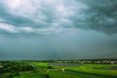 Nuvens de chuva sobre o campo com um lago fotos de stock