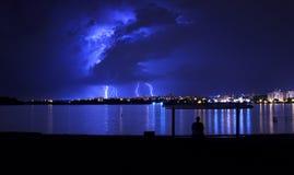 Nuvens de tempestade com relâmpago e um homem que senta-se sob um telhado no banco de rio Imagens de Stock Royalty Free