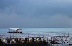 Nuvens de tempestade do cais e do flutuador Imagem de Stock Royalty Free