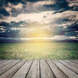 Nuvens de tempestade e prado do campo com tabela de madeira Imagem de Stock Royalty Free