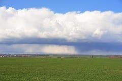 Nuvens de tempestade sobre o campo verde Fotos de Stock Royalty Free
