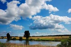 Nuvens do verão sobre a lagoa O meio do verão, no lago imagem de stock