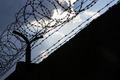 Nuvens dramáticas atrás da cerca do arame farpado na parede da prisão Fotografia de Stock Royalty Free