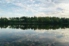 Nuvens e árvores refletidas espelho na água fotos de stock royalty free