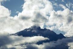 Nuvens em torno do cume da montanha Foto de Stock