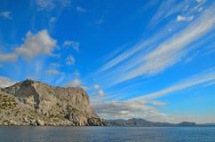 Nuvens em um céu azul, as montanhas rochosas bonitas nas costas do Mar Negro em Crimeia Fotos de Stock Royalty Free