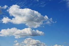 Nuvens em um fundo azul brilhante em um dia ensolarado Fotografia de Stock