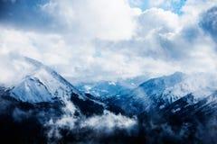 Nuvens em uma cordilheira nevado Imagem de Stock Royalty Free