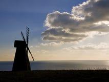 Nuvens escuras ausentes de sopro da silhueta do moinho de vento Fotografia de Stock