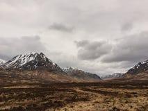 Nuvens escuras e cores bonitas sobre o Quiraing em Escócia - grama marrom e tempo nebuloso foto de stock
