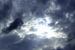 Nuvens escuras, sinistras que cercam a luz solar imagem de stock