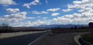 Nuvens, estrada e montanha fotografia de stock royalty free