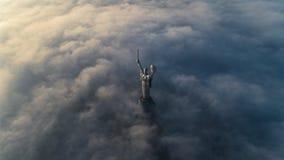 Nuvens grossas da névoa do outono e do monumento da pátria que cola fora deles foto de stock