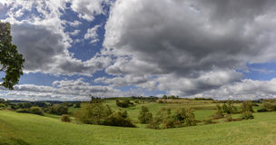 Nuvens grossas no campo verde da queda, Alemanha Foto de Stock