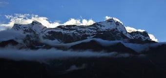 Nuvens iluminadas brilhantes sobre um cume da montanha imagem de stock royalty free