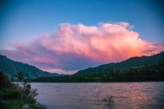 Nuvens pintadas pelos raios do sol de ajuste sobre as montanhas de Altai e o rio de Katun imagens de stock