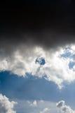 Nuvens pretas dramáticas escuras sobre o céu azul imagem de stock royalty free