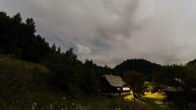 nuvens que movem-se sobre a casa de campo na noite - noite romântica na cabine de madeira com Lua cheia - timelapse da natureza b filme