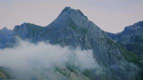 Nuvens que passam sobre os picos de montanha video estoque