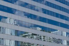 Nuvens refletidas nos indicadores do prédio de escritórios Foto de Stock