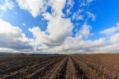 Nuvens sobre o close-up da terra arável Foto de Stock Royalty Free