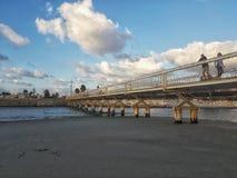 Nuvens sobre uma ponte que cruza um rio imagens de stock