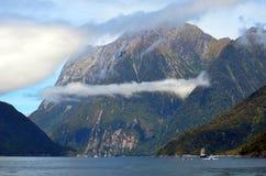 Nuvola bassa e nave alta su Milford Sound, Nuova Zelanda Fotografia Stock Libera da Diritti